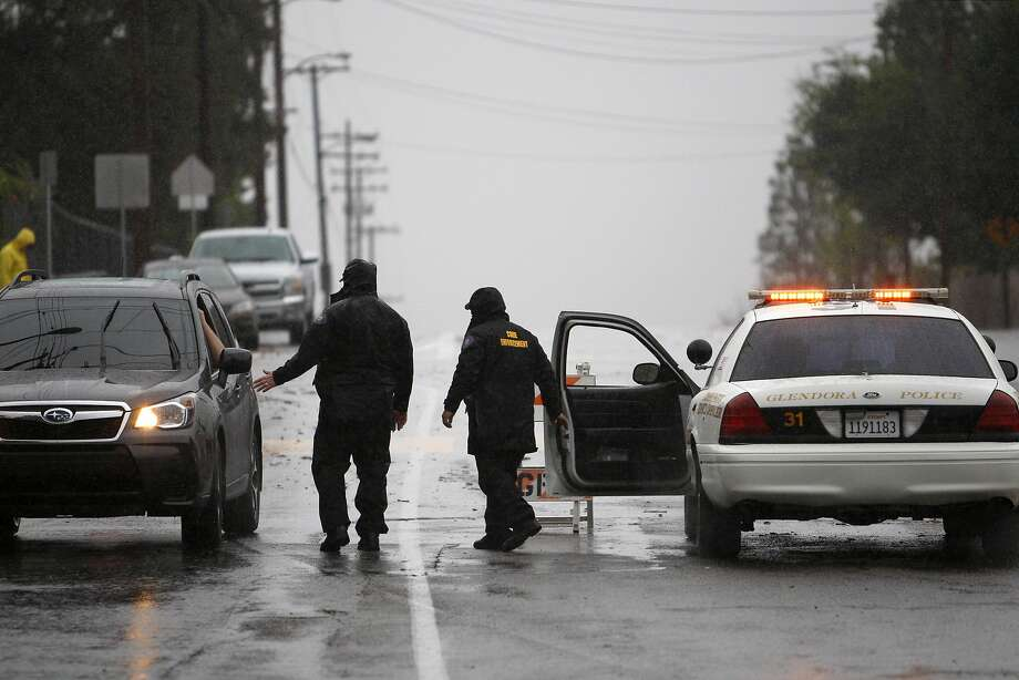 A roadblock keeps people from entering an evacuated neighborhood below the Colby Fire burn area as a storm brings rain in the midst of record drought on February 28, 2014 in Glendora, California. The rain offers some relief to the dry conditions but is not expected to be enough to break the historic drought. A drought-related unseasonal wildfire, the Colby Fire, was accidentally ignited in the dry chaparral vegetation in January, destroying homes and sending thousands fleeing. The charred and denuded hillsides are threatening the homes of about a thousand evacuated residents with rain-loosened mud-ash debris flows.  Photo: David McNew, Getty Images