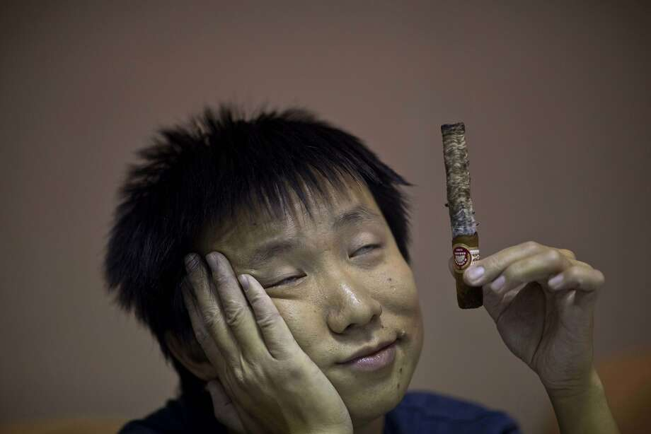 Exactly what kind of tobacco is in that cigar? A contestant in the longest-ash competition waits for his stogie to burn down during the XVI Cuba Cigar festival in Havana. Photo: Ramon Espinosa, Associated Press