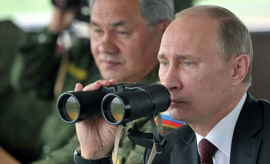 Russia's President Vladimir Putin (right) and Defense Minister Sergei Shoigu watch military exercises in this 2013 file photo. Putin has ordered combat readiness drills near the Ukrainian border, which raised fears of the Kremlin using its military muscle to sway the outcome of a three-month crisis that has pitted Moscow against the West in a Cold War-style confrontation over the future of the strategic nation of 46 million. Photo: Alexei Nikolsky / AFP/Getty Images / AFP ImageForum