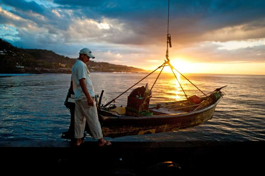 El Salvador: A fisherman prepares for a fishing trip in La Libertad, 35 km south of San Salvador, El Salvador on February 23, 2014. The fishing industry has grown some 45% in the last 15 years in Central America. Photo: JOSE CABEZAS, AFP/Getty Images