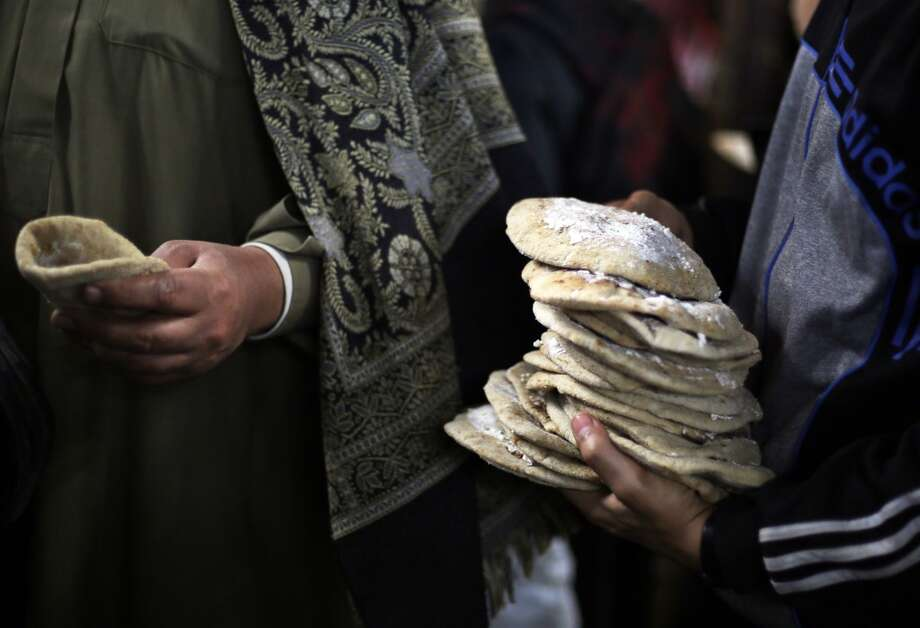 "Egypt: A boy distributes breads with meat and cheese to worshippers after El Ishaa prayers at the Al-Hussein mosque, during celebration day of ""Moulid Al-Hussein"" the birthday of Prophet Mohammad's grandson Hussein in Cairo, February 25, 2014. Photo: AMR ABDALLAH DALSH, Reuters"