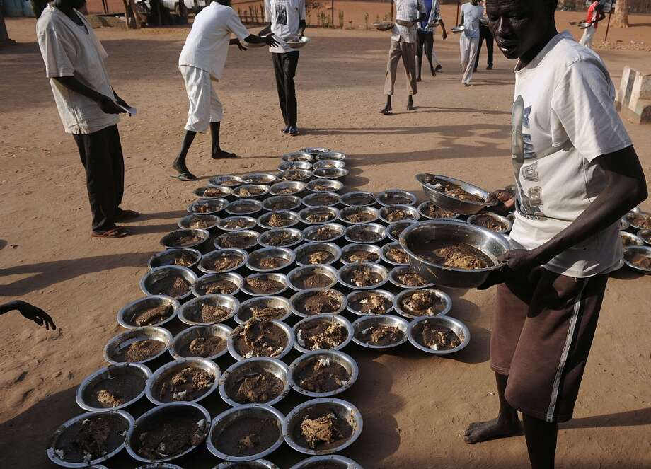 Sudan: Inmates distribute the dinner, served in bowls, to be shared among prisoners at the central prison in Rumbek, Lakes state, South Sudan, on February 19, 2014. Independent for nearly three years as of mid-last December when South Sudan fell into wide-spread, deadly ethnic violence the shortlived peace is seen to be sacrificed at the altar of a corrupt albeit fledgling government. Influenced principally by the two largest ethnic groups, Dinka and Nuer respectively, also traditionally fierce rivals -- government efforts to contain simmering intercommunal resentment, led to rifts within the ruling SPLM, according to US special envoy to Sudan and South Sudan, Donald Booth. Photo: TONY KARUMBA, AFP/Getty Images