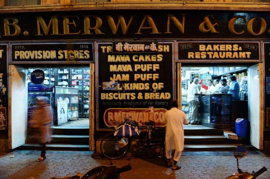 India: In this photograph taken on February 17, 2014, Indian customers buy mawa cakes and bread at the B. Merwan & Co. Irani cafe in Mumbai. In the late 19th and early 20th centuries, hundreds of eateries known as Irani cafes sprouted up in Mumbai due to a wave of Persian immigration. One of the most famous of the remaining few is now set to close. Photo: INDRANIL MUKHERJEE, AFP/Getty Images
