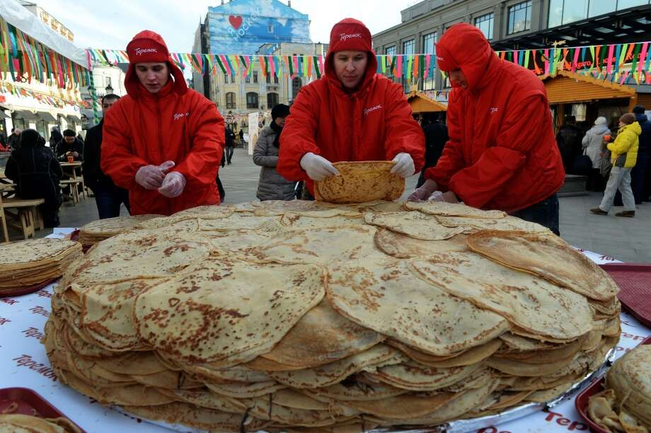 Russia: Employees of a fast food chain prepare to serve free pancakes during their action to mark Maslenitsa, or Shrovetide, in central Moscow, on February 26, 2014. Maslenitsa is a week long traditional carnival of saying goodbye to the already passed winter in Russia, Belarus and Ukraine. Photo: Vasily Maximov, AFP/Getty Images