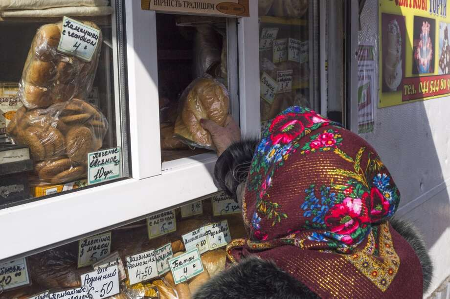 Ukraine: A woman purchases a loaf of fresh bread from a kiosk in Kiev, Ukraine, on Thursday, Feb. 26, 2014. Photo: Vincent Mundy, Bloomberg