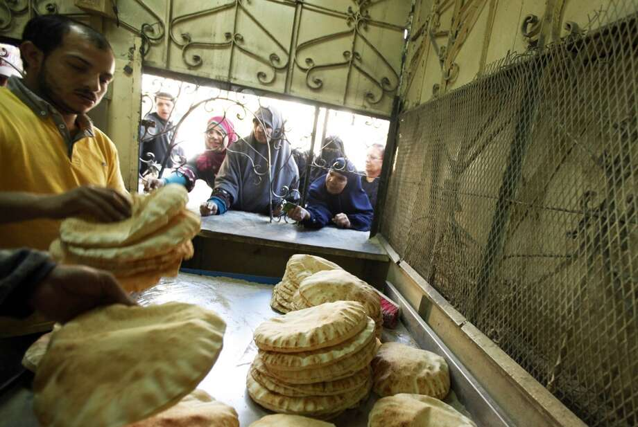 Egypt: People queue for subsidised bread at a bakery equipped with a smart card system in the Suez Canal city of Port Said, 170 km (106 miles) northeast of Cairo, February 24, 2014. A device resembling a credit card swiper is revolutionizing some of Egypt's politically explosive bread lines and may help achieve the impossible -- cutting crippling food import bills. Authorities who hope to avoid protests over subsidized loaves sold for the equivalent of one U.S. cent have turned to smart cards to try to manage the corrupt and wasteful bread supply chain that has been untouchable for decades. Picture taken February 24, 2014. Photo: MOHAMED ABD EL GHANY, Reuters