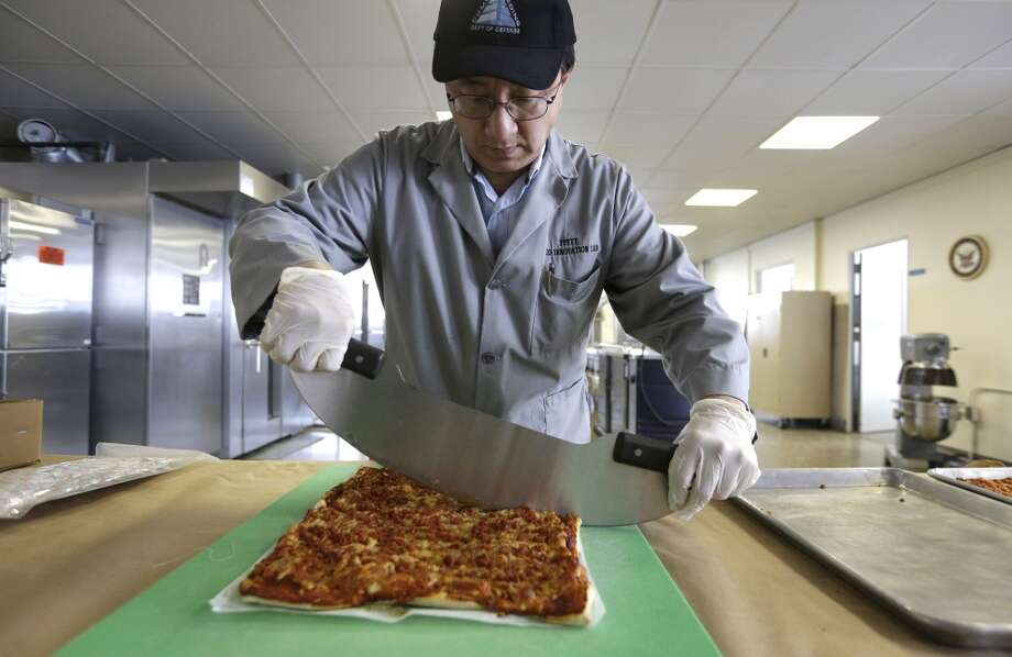 Massachusetts: In this Thursday, Feb. 6, 2014 photo, food technologist Tom Yang cuts a prototype pizza at the U.S. Army Natick Soldier Research, Development and Engineering Center, in Natick, Mass. Pizza is in development to be used in individual field rations known as meal ready to eat, or MREs. It has been one of the most requested options for soldiers craving a slice of normalcy in the battlefield and disaster areas. Photo: Steven Senne, Associated Press