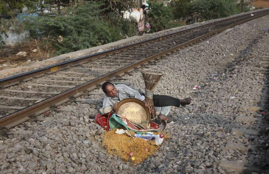 "India: An Indian food vendor falls and spills his bowl of Chudwa while crossing the railway tracks in Hyderabad, India, Thursday, Feb. 13, 2014. ""Chudwa"" is a rice flakes mixture served with a blend of nuts and dried fruits. Photo: Mahesh Kumar A., Associated Press"