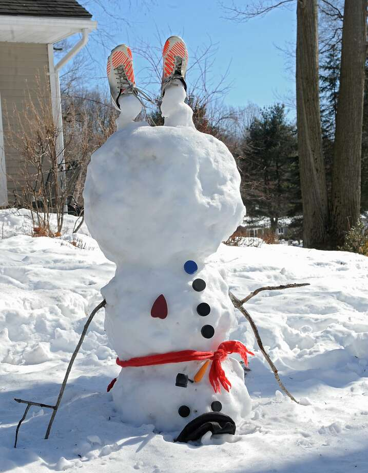 Topsy-turvy Frosty:A snowman does a headstand in Halfmoon, N.Y. Photo: Lori Van Buren, Albany Times Union