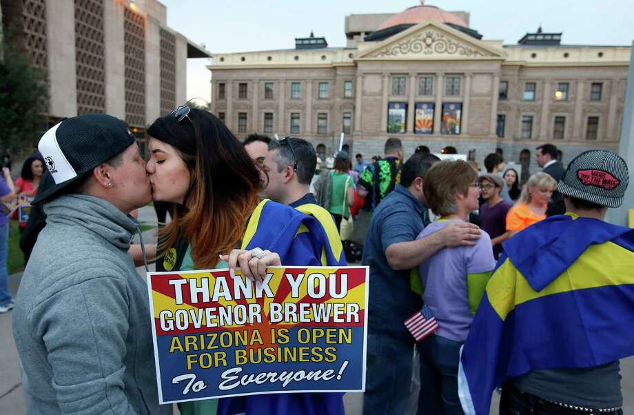 With the Arizona Capitol in the background, gay rights supporters Rachel Butas, right, and Jo Jo Halko kiss after the two learn that Arizona Gov. Jan Brewer announces she has vetoed SB1062, a bill designed to give added protection from lawsuits to people who assert their religious beliefs in refusing service to gays, on Wednesday, Feb. 26, 2014, in Phoenix. (AP Photo/Ross D. Franklin) ORG XMIT: AZRF134 Photo: Ross D. Franklin / AP