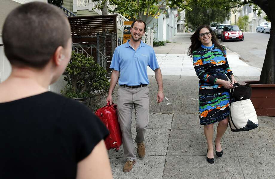 Andrew Kitchell, Co-founder and director of operations at Beyond Stays, center, helps Airbnb renter Andrea Minkow, right, with her bags to the rental home in San Francisco, Calif., on Thursday, February 27, 2014l, as Carina Cassone, left, waits to greet them. Beyond Stays, is one of many full-service companies, that take over the the duties of an Airbnb host, and was greeting Airbnb guest Andrea Minkow who is renting a house in the Castro. Kitchell gave her a tour of the home, the key, a gift basket, and instructions for Minkow's stay. Photo: Carlos Avila Gonzalez, The Chronicle