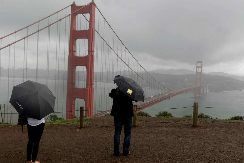 Tourists admire the view of the Golden Gate Bridge in the rain from the Marin Headlands on Friday, Feb. 28, 2014. Stormy weather continues to drench the Bay Area, but will hardly make a dent in the drought conditions.