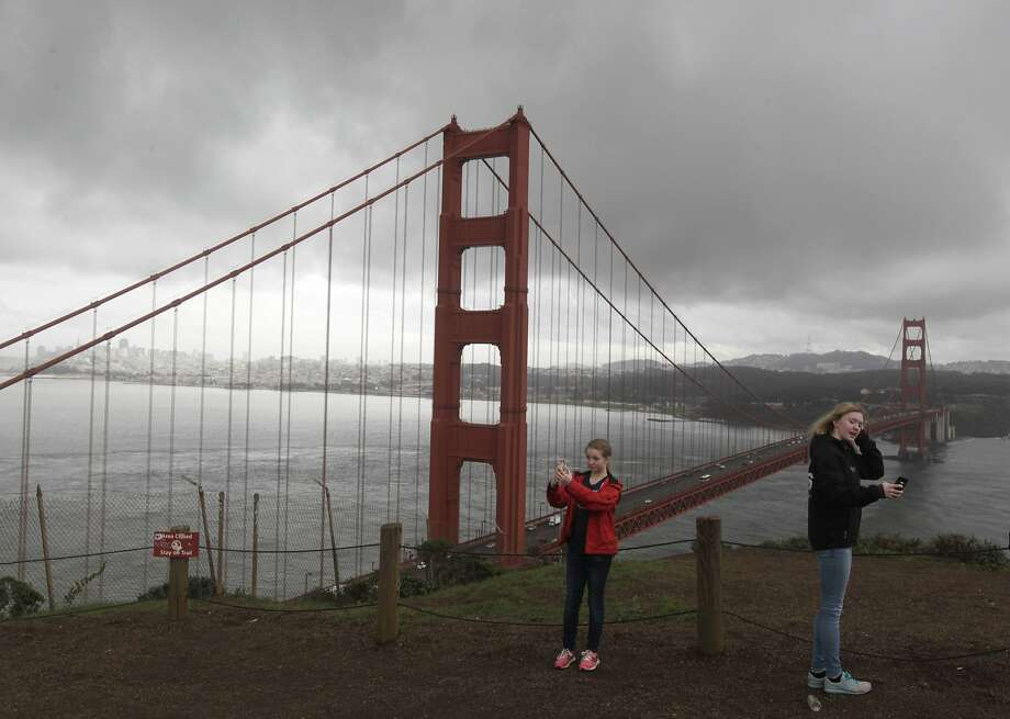Visiting from Sweden, Tilde Gulliksson (left), 12, and her sister Emmy, 15, take selfies during a break in the rain at the Marin Headlands on Friday, Feb. 28, 2014. Stormy weather continues to drench the Bay Area, but will hardly make a dent in the drought conditions. Photo: Paul Chinn, The Chronicle