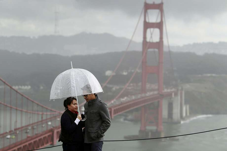 Visiting from Las Vegas, Gee Olivar (left) and her boyfriend Dax Timbol stop at the Marin Headlands in the rain on Friday, Feb. 28, 2014. Stormy weather continues to drench the Bay Area, but will hardly make a dent in the drought conditions. Photo: Paul Chinn, The Chronicle