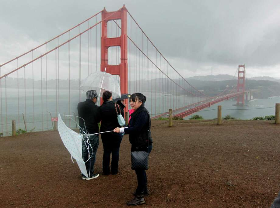 The wind was too much for Gee Olivar's umbrella during her visit to the Marin Headlands in February 2014. Photo: Paul Chinn / The Chronicle / ONLINE_YES