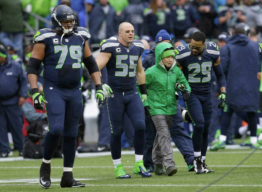 Seattle Seahawks defensive end Red Bryant (79),  linebacker Heath Farwell (55) and free safety Earl Thomas (29) walk onto the field with Kellen Joyce for the opening coin toss before an NFC divisional playoff NFL football game against the New Orleans Saints in Seattle, Saturday, Jan. 11, 2014. (AP Photo/Ted S. Warren) Photo: Ted S. Warren, STF / AP