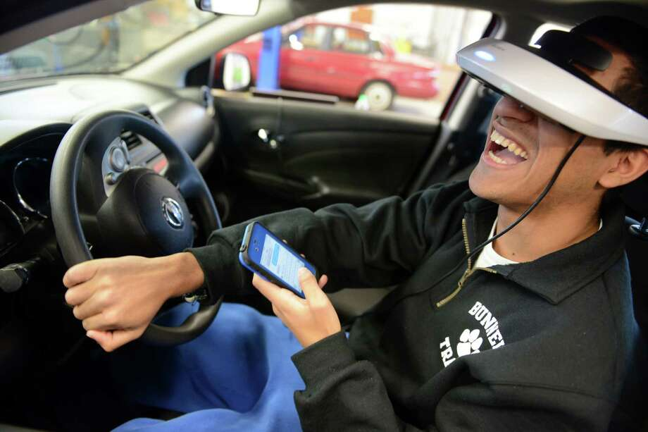 Senior Eduardo Carmelo attempts to text and drive using a driving simulator to test the difference between driving and driving while texting Friday, Feb. 28, 2014, in the auto shop at Bunnell High School in Stratford, Conn. Photo: Autumn Driscoll / Connecticut Post