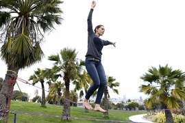 Lauren Crepeau walks a slack line at Dolores Park in San Francisco, Calif., on Thursday, February 27, 2014.  Dolores Park, one of the most popular spots in the city, is closing Saturday for more than a year of rehab work and upgrades.