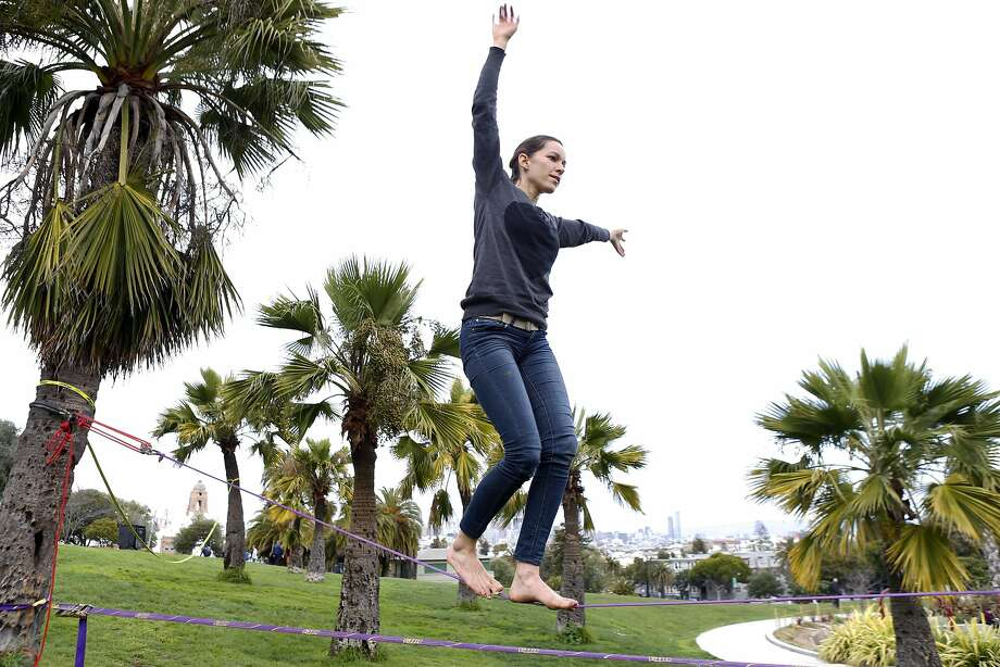 Lauren Crepeau walks a slack line at Dolores Park in San Francisco, Calif., on Thursday, February 27, 2014.  Dolores Park, one of the most popular spots in the city, is closing Saturday for more than a year of rehab work and upgrades. Photo: Carlos Avila Gonzalez, The Chronicle