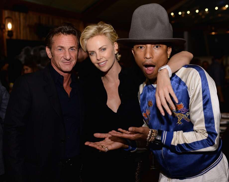 "Sean Penn and Charlize Theron pose with Pharrell Williams at Bionic Yarn, G-Star and Hennessy Privilege Celebrate Pharrell Williams and his Oscar nominated single, ""Happy"" on February 27, 2014 in Los Angeles, California. Photo: Dimitrios Kambouris, Getty Images For One View"