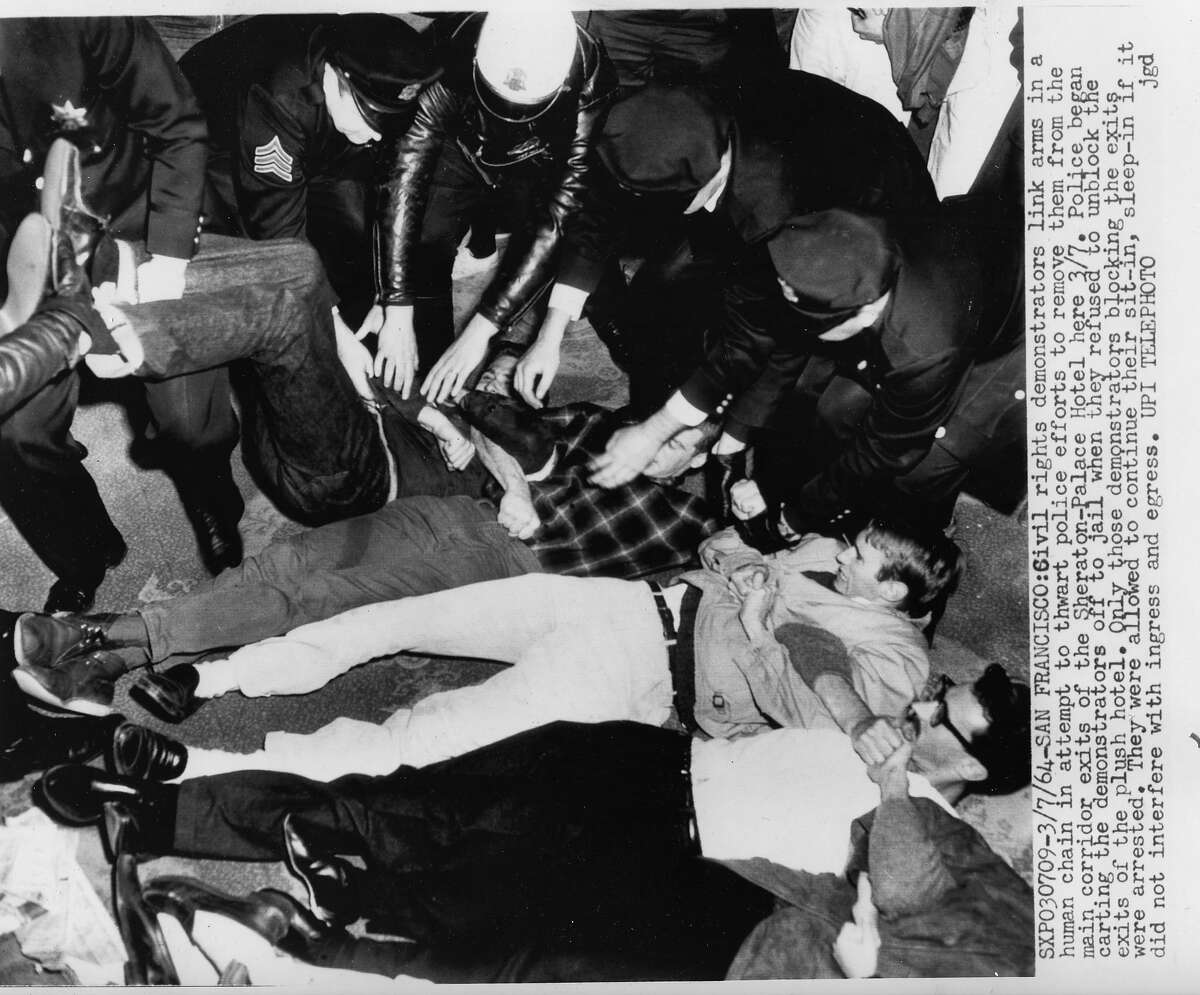 Civil rights demonstrators link arms in a human chain in an attempt to thwart police efforts to remove them from the main corridor of the Sheraton Palace hotel. The sit in and protest claimed discriminatory hiring practices. UPI photo shot dated March 7, 1964