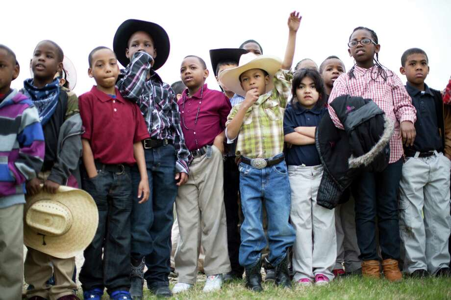 Damecko Williams, 7, Amarioe Shelvin, 8, and other B.C Elmore Elementary School students watch as the Northeastern Trail Riders arrive with horses and wagons to their school, Friday, Feb. 28, 2014, in Houston. Photo: Marie D. De Jesús, Houston Chronicle / © 2014 Houston Chronicle