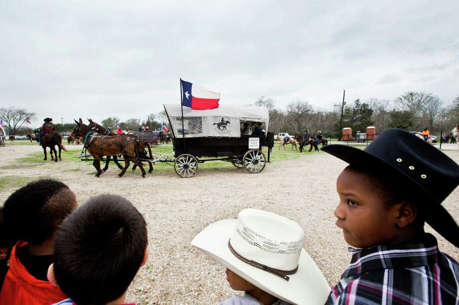 Amarioe Shelvin, left, 8, and Damecko Williams watch as the Northeastern Trail Riders arrive with their wagon and horses to their school B.C Elmore Elementary School,  Friday, Feb. 28, 2014, in Houston. Photo: Marie D. De Jesús, Houston Chronicle / © 2014 Houston Chronicle