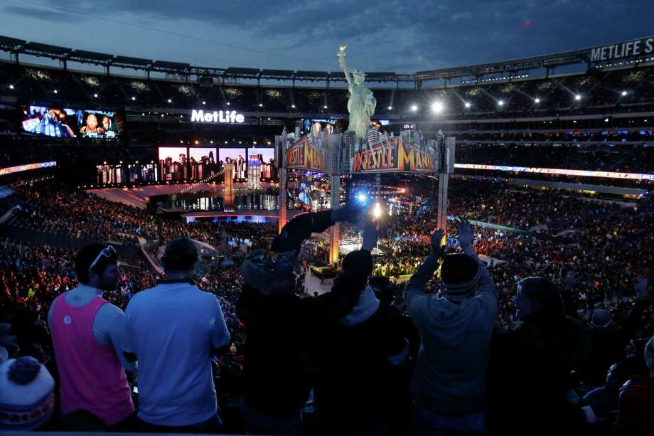 Fans watch the WWE Wrestlemania 29 wrestling event, Sunday, April 7, 2013, in East Rutherford, N.J. (AP Photo/Mel Evans). WWE will begin touring Japan with shows in July. Photo: Mel Evans, Associated Press / Stamford Advocate Contributed