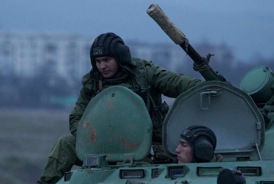 Soldiers sit atop a Russian armored personnel carrier near the town of Bakhchisarai, Ukraine, Friday, Feb. 28, 2014. A convoy of Russian vehicles was parked on the side of the road near the town of Bakhchisarai, apparently because one of them had mechanical problems. Photo: Ivan Sekretarev, AP / AP
