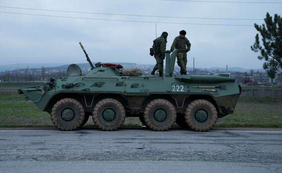 Soldiers stand atop a Russian armored personnel carrier near the town of Bakhchisarai, Ukraine, Friday, Feb. 28, 2014. The vehicles were parked on the side of the road near the town of Bakhchisarai, apparently because one of them had mechanical problems. Photo: Ivan Sekretarev, AP / AP