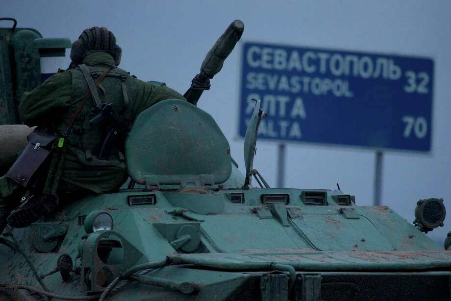"""A soldier rests atop a Russian armored personnel carriers with a road sign reading """"Sevastopol - 32 kilometers, Yalta - 70 kilometers"""", near the town of Bakhchisarai, Ukraine, Friday, Feb. 28, 2014. The vehicles were parked on the side of the road near the town of Bakhchisarai, apparently because one of them had mechanical problems. Photo: Ivan Sekretarev, AP / AP"""
