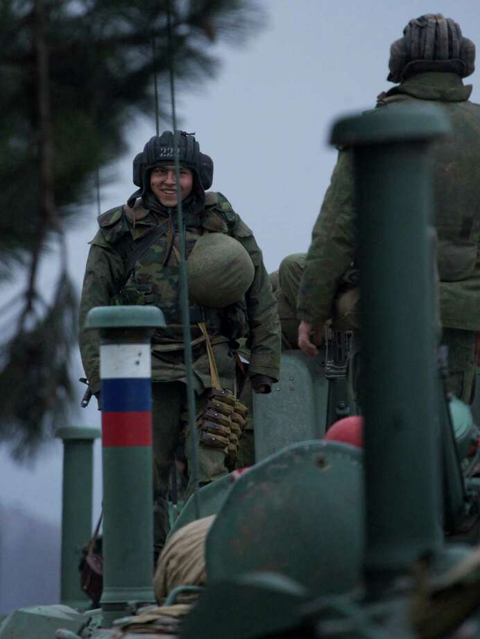 A soldier smiles as he stands atop a Russian armored personnel carrier near the town of Bakhchisarai, Ukraine, Friday, Feb. 28, 2014. The vehicles were parked on the side of the road near the town of Bakhchisarai, apparently because one of them had mechanical problems. Photo: Ivan Sekretarev, AP / AP