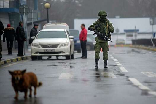 An unidentified armed man patrols a square in front of the airport in Simferopol, Ukraine, Friday, Feb. 28, 2014. Russian military were blocking the airport in the Black Sea port of Sevastopol in Crimea near the Russian naval base while unidentified men were patrolling another airport serving the regional capital, Ukraine's new Interior Minister Arsen Avakov said on Friday. Photo: Andrew Lubimov, AP / AP