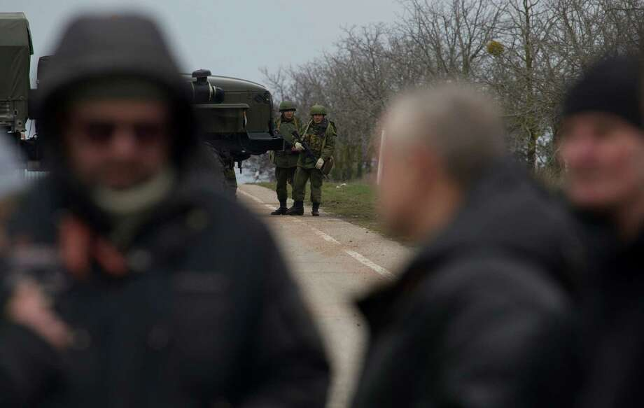 Unidentified gunmen block the road toward the military airport at the Black Sea port of Sevastopol in Crimea, Ukraine, Friday, Feb. 28, 2014, as local residents are seen, in foreground. Russian troops took control of the two main airports in the strategic peninsula of Crimea, Ukraine's interior minister charged Friday, as the country asked the U.N. Security Council to intervene in the escalating conflict. Russian state media said Russian forces in Crimea denied involvement. No violence was reported at the civilian airport in Crimea's capital of Simferopol or at the military airport in the Black Sea port of Sevastopol, also part of Crimea. At the Simferopol airport, a man claiming to speak for the camouflage-clad forces patrolling the airport described them as Crimean militiamen. Photo: Ivan Sekretarev, AP / AP