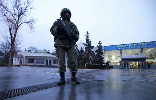 An unidentified armed man patrols a square in front of the airport in Simferopol, Ukraine, on Friday, Feb. 28, 2014.  Dozens of armed men in military uniforms without markings occupied the airport in the capital of Ukraine's strategic Crimea region early Friday. Photo: Ivan Sekretarev, AP / AP