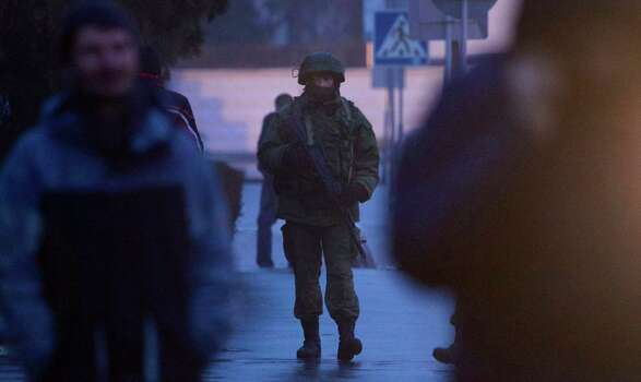 An unidentified armed man patrols a square in front of the airport in Simferopol, Ukraine, Friday, Feb. 28, 2014.  Dozens of armed men in military uniforms without markings occupied the airport in the capital of Ukraine's strategic Crimea region. Photo: Ivan Sekretarev, AP / AP