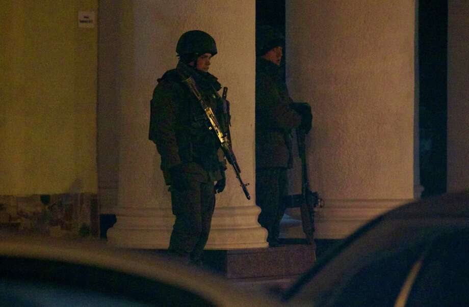 Unidentified armed men guard a building at the airport in Simferopol, Ukraine, on Friday, Feb. 28, 2014. Dozens of armed men in Russian-style military uniforms occupied the airport in the capital of Ukraine's strategic Crimea region early Friday. Photo: Ivan Sekretarev, AP / AP