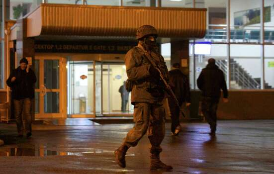 An unidentified armed man patrols a square in front of the airport in Simferopol, Ukraine, Friday, Feb. 28, 2014.  Dozens of armed men in military uniforms without markings occupied the airport in the capital of Ukraine's strategic Crimea region early Friday. Photo: Ivan Sekretarev, AP / AP