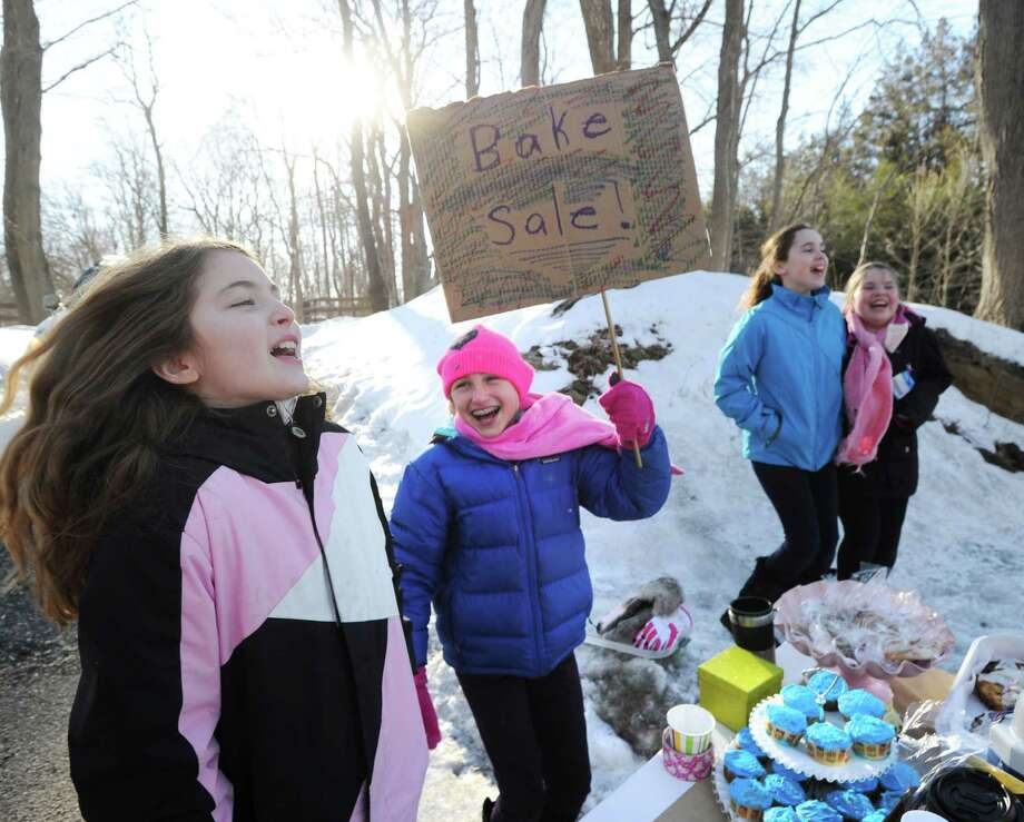 North Street School fourth-grade students, from left, Rebecca Falus, 10, Stephanie Clifford, 11, Olivia Burton, 10, and Catherine Duffy, also 10, all of Greenwich, shout for passing vehicles to stop while having a bake sale on Bedford-Banksville Road in Banksville, N.Y., Friday afternoon, Feb. 28, 2014. The activity was taking place at the home of Samantha Knapp, who is the aunt of Maddy Wright, one of the students involved. Knapp said that the money raised will be donated to a charity yet to be chosen. Photo: Bob Luckey / Greenwich Time