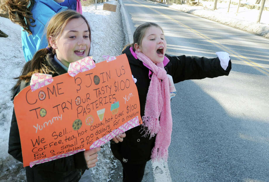 North Street School fourth-grade students, Maddy Wright, left, and Catherine Duffy, both 10, both of Greenwich, hold a sign as they shout for passing vehicles to stop while selling pastries and hot drinks on Bedford-Banksville Road in Banksville, N.Y., Friday afternoon, Feb. 28, 2014. The activity was taking place at the home of Samantha Knapp, who is the aunt of Maddy Wright, one of the students involved. Knapp said that the money raised will be donated to a charity yet to be chosen. Photo: Bob Luckey / Greenwich Time