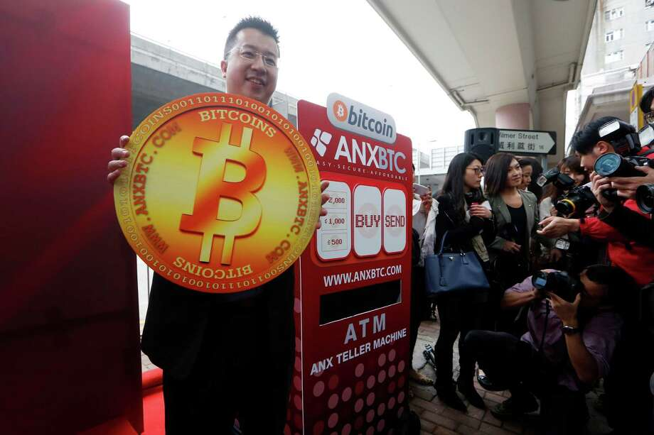 Ken Lo, CEO of the ANXBTC bitcoin exchange in Hong Kong, holds a cardboard Bitcoin during the opening ceremony of a Bitcoin retail store Friday.  The store opened despite the virtual currency facing much scrutiny over the last week. Photo: Kin Cheung, STF / AP
