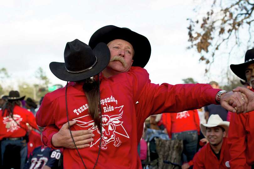 Jeff Simpson, trail boss of the Texas Independence Trail Riders, is embraced by his wife after the g
