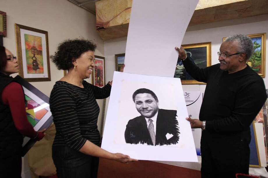 Owner Robbie Lee admires a portrait of Mickey Leland by artist Leonard Freeman, right, at the Black Heritage Gallery. Photo: Mayra Beltran, Staff / © 2014 Houston Chronicle