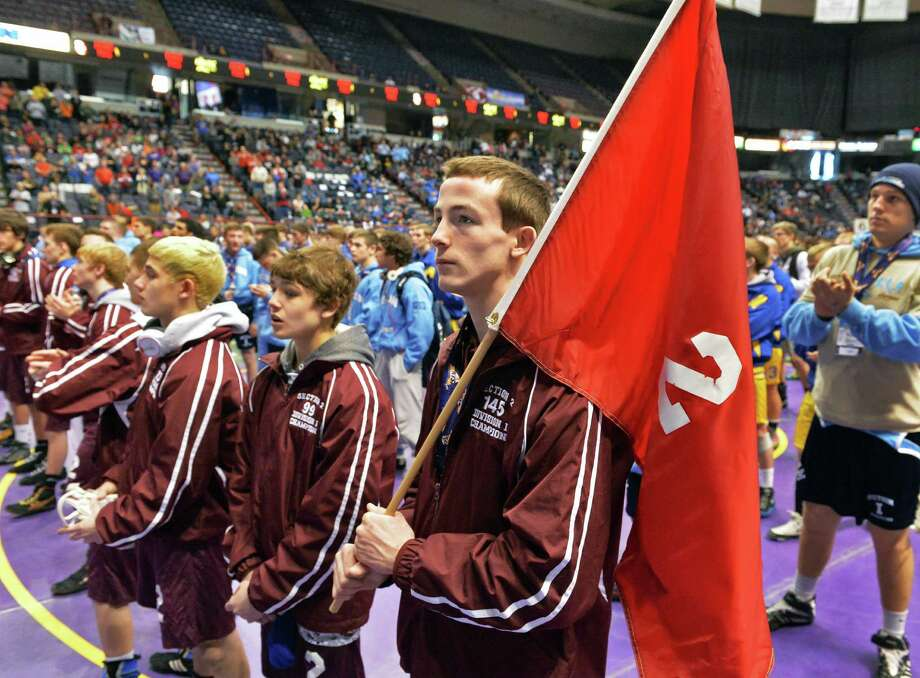 Burnt Hills wrestler Joey Butler, center, holds the Section 2 flag during opening ceremonies for the State wrestling high school tournament Friday morning, Feb. 28, 2014, at the Times Union Center in Albany, N.Y.  (John Carl D'Annibale / Times Union) Photo: John Carl D'Annibale / 00025917A
