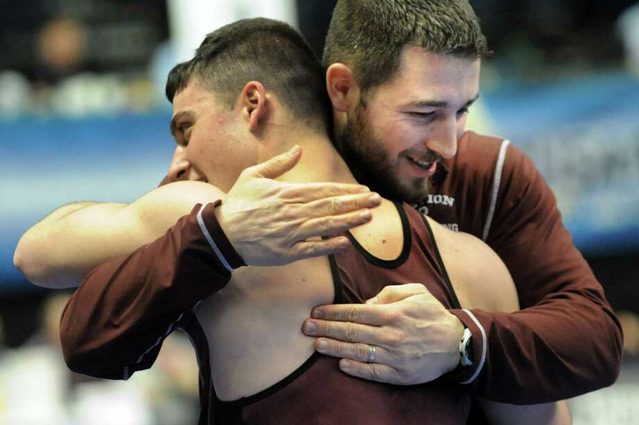 Hudson Falls' Geno Brancati, left, embraces coach Mike Prendergast after winning in the 170-weight class in Division II during the quarterfinals of the State Wrestling Tournament on Friday, Feb. 28, 2014, at Times Union Center in Albany, N.Y. (Cindy Schultz / Times Union) Photo: Cindy Schultz / 00025917B