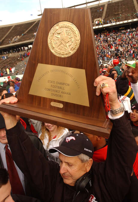 North Shore coach David Aymond hoists the 2003 Class 5A Division I trophy after a win over The Woodlands at Rice Stadium. The win marked a highlight in a 20-year coaching run that saw Aymond turn the Mustangs from a program that never reached the playoffs into a perennial state contender. Photo: Christobal Perez, STF / Houston Chronicle