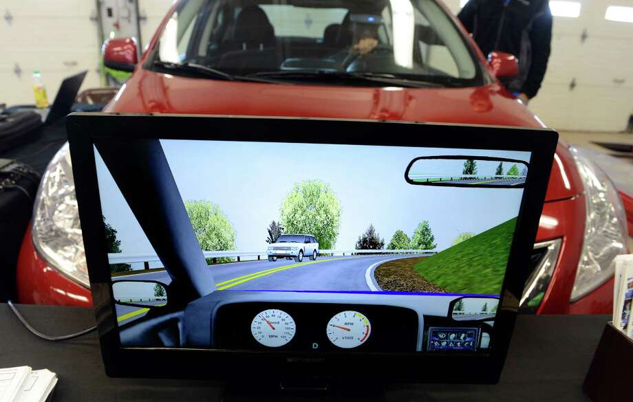 A monitor shows student Katelyn Carlson's trajectory as she uses a driving simulator to test the difference between driving and driving while texting Friday, Feb. 28, 2014, in the auto shop at Bunnell High School in Stratford, Conn. Photo: Autumn Driscoll / Connecticut Post