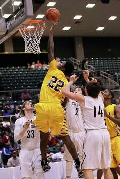 Marshall's Elliot Taylor attempts to tap in an offensive rebound over Nederland's Tyler Toon (2) and Colton Kimler (14) during action from a Class 4A Region III boys basketball semifinal game Friday, Feb. 28, 2014 at the Merrill Center. Fort Bend Marshall won 53-50. Photo: Bob Levey / ©2014 Bob Levey