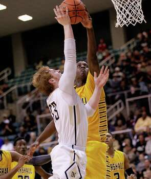 Nederland's Colton Weisbrod, left, had his shot blocked by Marshall's Elliot Taylor during action from a Class 4A Region III boys basketball semifinal game Friday, Feb. 28, 2014 at the Merrill Center. Fort Bend Marshall won 53-50. Photo: Bob Levey / ©2014 Bob Levey
