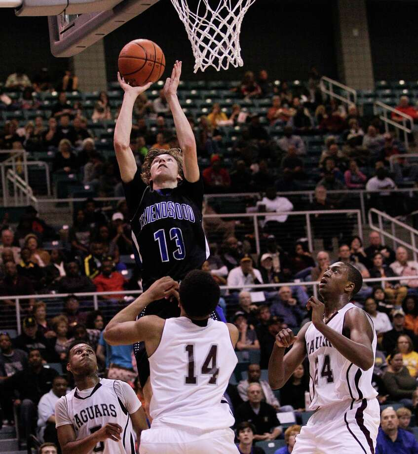 Friendswood's Garrett Cragin drives to the basket over Beaumont Central's Garrison Mitchell (14)  and E'Torrion Wilridge (24) during action from a Class 4A Region III boys basketball semifinal game Friday, Feb. 28, 2014 at the Merrill Center. Beaumont Central won 46-45. Photo: Bob Levey / ©2014 Bob Levey